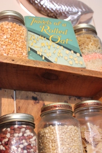 Jars of dried beans on a shelf, and a book called Travels of a Rolled Oat.