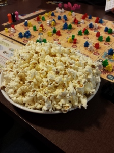 Bowl of popcorn with a board game in the background