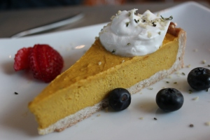 Slice of pumpkin pie on a place with fruit on the side