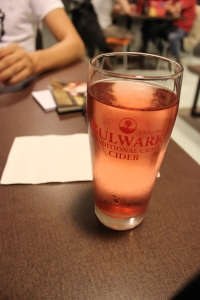 A glass of pinkish cider on the table